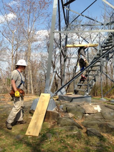 Photo of men carrying lumber for the new floor of the fire tower cabin up the stairs